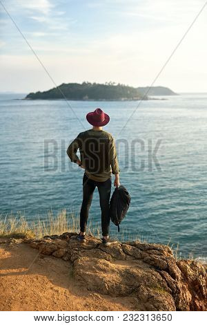 Young Man With A Black Backpack Stands On The Cliff And Looks At The Small Green Islands In The Sea.