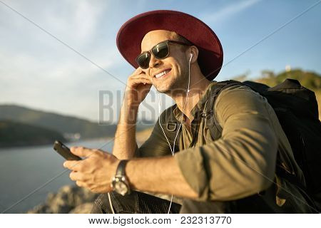 Pretty Smiling Guy In Sunglasses Is Listening Music While Sitting On The Cliff On The Sunny Backgrou