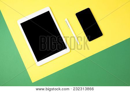 Digital Tablet Computer And Mobile Phone On Yellow And Green Background. Top View