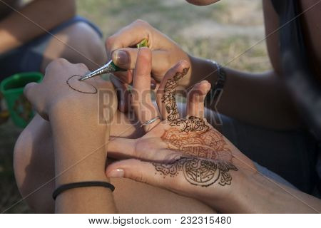 A Man Making Temporary Henna Tattoo On Woman's Wirst