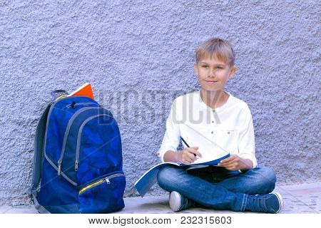 Child Sitting On The Ground Outdoors And Doing School Homework