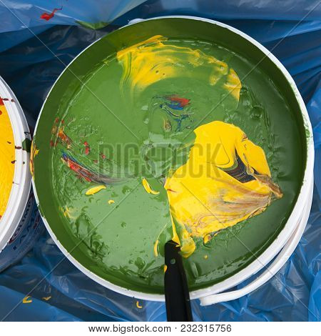 The Paint Buckets With Yellow And Green Colors