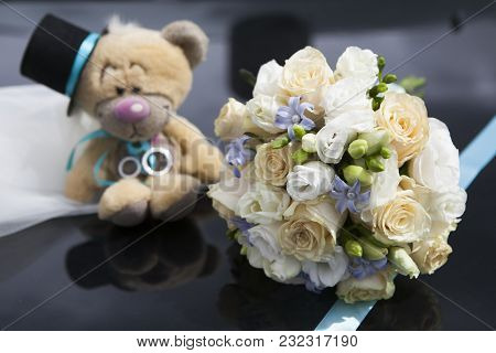 The Bride S Bouquet Of Cream Roses, White Freesias And Pearls Lies On The Car