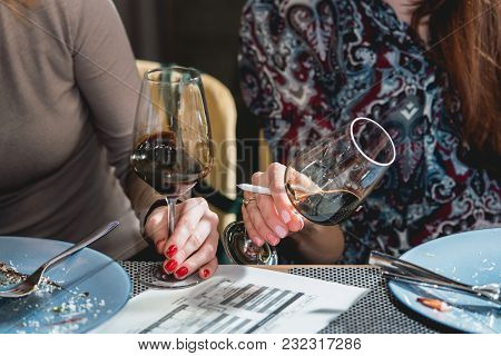 Woman Holds Glass Of Red Wine. Glasses On The Table At Wine Tasting. People Consider The Color Of Th