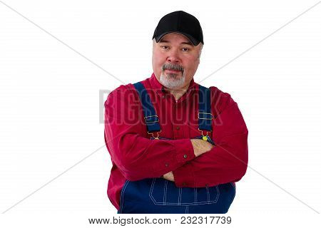 Portrait Of Man Wearing Dungarees Standing With Arms Crossed Against White Background