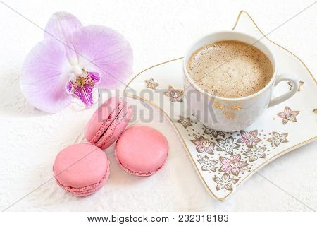 Pink Macaroon With Strawberry Cream, Orchid And Cup Of Coffee With Milk On White Textured Background