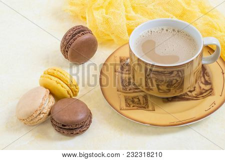 Yellow And Brown Macaroon With Ganache, Citrus And Vanilla Cream, Cup Of Coffee With Milk On Light Y