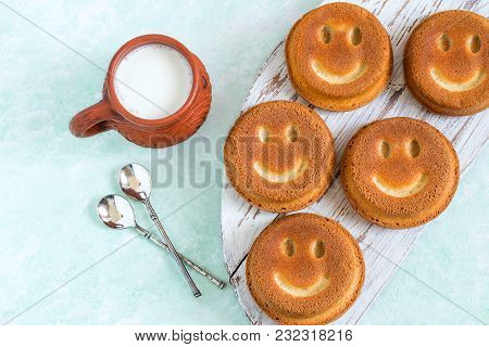 Funny Cupcakes In Form Of Smiling Face And Mug With Milk. Food That Causes Positive Emotions. Humoro