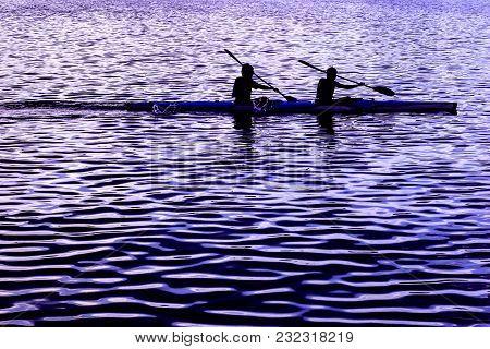Two Sportsmen On Canoeing At Silhouette Scene