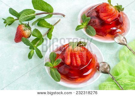 Delicious Strawberry Jelly With Whole Berries On Plate On Light Green Background. Served With Fresh