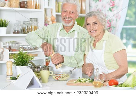 Happy Senior Couple Preparing Dinner Together With Tablet On Table