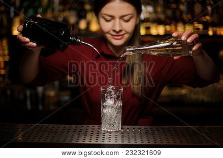 Young Female Bartender Poting Gin And Sweet Syrup Into A Glass For Making A Fresh Summer Cocktail