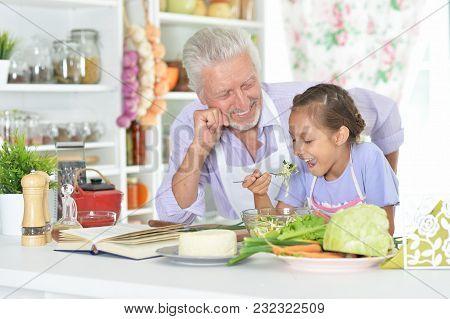 Portrait Of Senior Man With Granddaughter Preparing Dinner In Kitchen