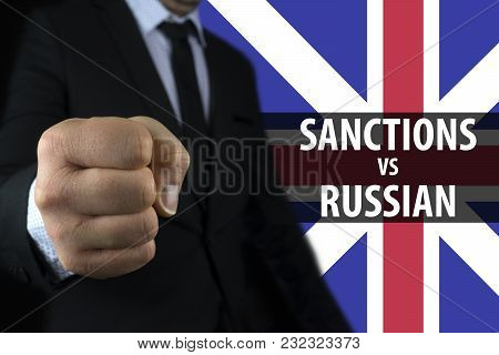 Businessman Shows A Fist Against The Background Of The English Flag And An Inscription Of Sanctions