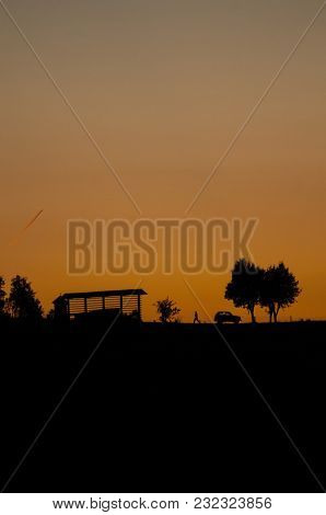 Silhouette Of A Rural Scene Right After Sunset With Orange Sky In The Background