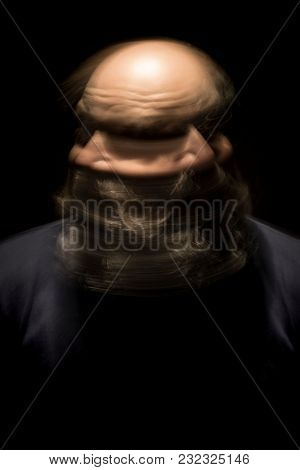 An image of a motion blur portrait of a bearded bald head man