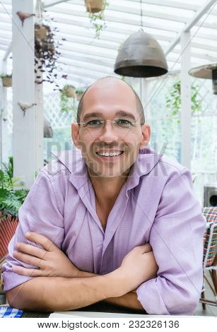 Attractive And Cheerful Bald Man Wearing Glasses And An Earring In One Ear Sitting At A Table On The