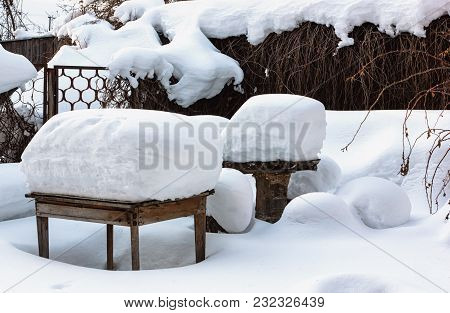 Rustic Wooden Tables And Bench In The Yard Under A Thick Layer Of Snow After A Snowfall On A Winter
