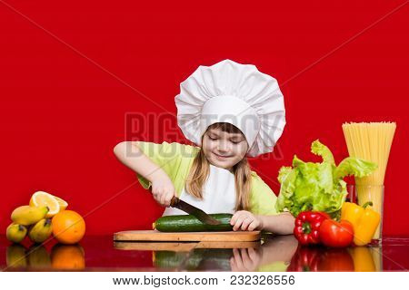 Happy Little Girl In Chef Uniform Cuts Vegetables In Kitchen. Kid Chef. Cooking Process Concept