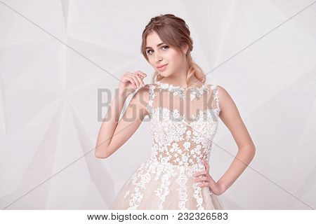 Beautiful Woman Wearing In Luxurious Long Wedding Dress. Concept Of Wedding Hairstyle, Makeup And Ac