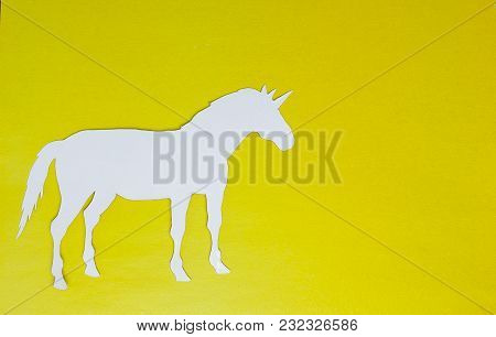 White Unicorn With Paper On A Yellow Background.