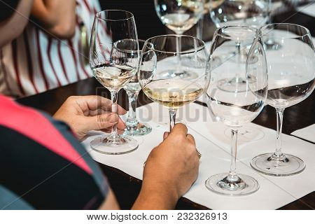 Woman Holds Two Glasses Of White Wine. A Lot Of Different Wine Glasses On The Table At Wine Tasting.