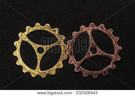 Two metal cogwheels in different colors interlocking. Cooperation and group work concept.