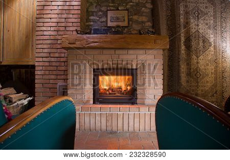 Moody Fireplace Indoor, With Two Green Armchairs, And Home-like Ornaments Around.
