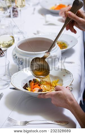 Elegant White Laid Table With Lunch. Ladle Of Soup With Vegetables. Glass With White Wine.