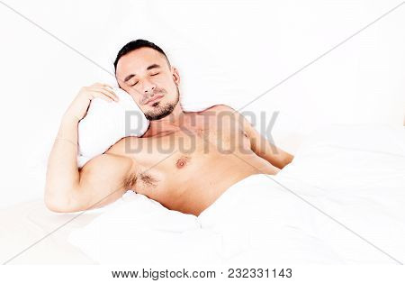 Man With Naked Torso Lying In Bed And Sleeping
