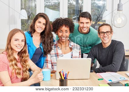 Group students as successful internet start-up team with laptop computer