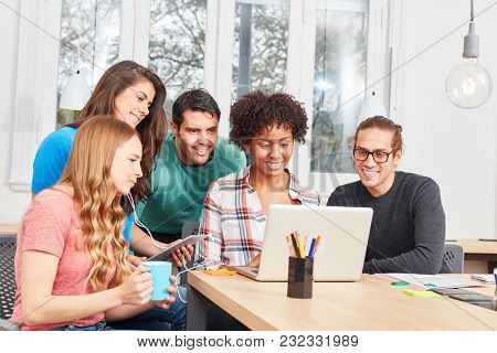 Student team in an IT workshop is learning together on laptop computer