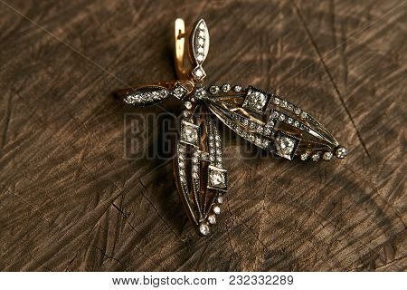 Golden Earring With Diamonds On Wooden Background. Luxury Female Jewelry Close-up