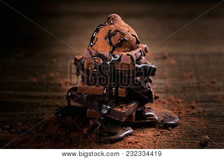 Chocolate Syrup Dripping On Stack Of Dark And Milk Chocolate Stack, Truffles. Chocolate With Cocoa P