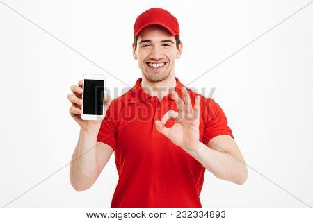 Portrait of a excited happy young delivery man in red cap standing isolated over white background. Looking camera showing display of mobile phone make okay gesture.