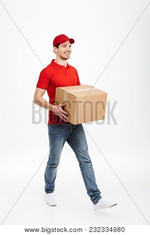Image of a handsome young delivery man in red cap walking with parcel post box isolated over white background. Looking aside.