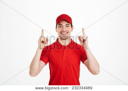 Image of a smiling young delivery man in red cap standing pointing isolated over white background. Looking camera.