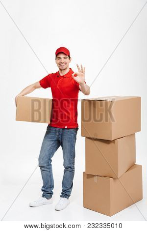Image of a handsome cheerful young delivery man in red cap standing with parcel post boxes isolated over white background. Looking camera with okay gesture.