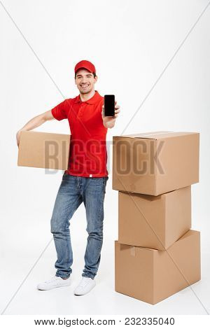 Image of a handsome happy young delivery man in red cap standing with parcel post boxes isolated over white background. Looking camera showing display of mobile phone.
