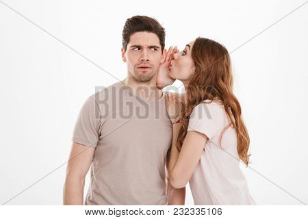 Photo of cute woman with beautiful long brown hair saying breathtaking rumors or news in ear of caucasian muscular man isolated over white background