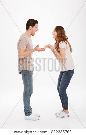 Full length photo of amazing adult guy and girl wearing beige t-shirts expressing delight standing face to face and gesturing on each other over white background