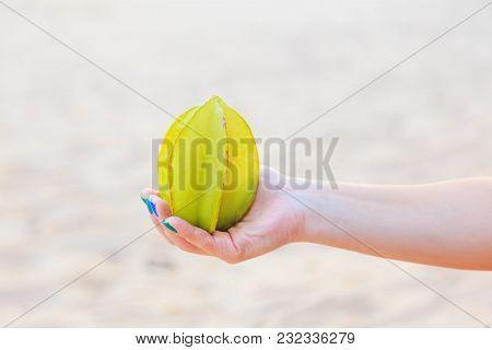 Female Hand Holding The Whole Exotic Yellow Green Carambola Fruit