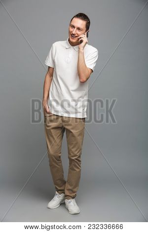 Image of cheerful young man standing isolated over grey wall. Looking aside talking by mobile phone.