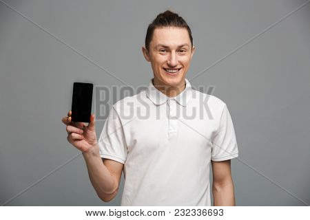 Image of handsome young man standing isolated over grey wall. Looking camera showing display of mobile phone.