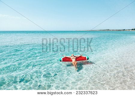 Woman on lilo in the sea water. Girl relaxing on inflatable ring on the beach. Summer vacations, idyllic scene.