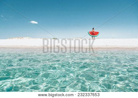 Man on lilo in the sea water. Human relaxing on inflatable ring on the beach. Summer vacations, idyllic scene.