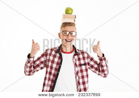 Portrait of an excited schoolboy in eyeglasses holding stack of books and green apple on his head and showing thumbs up isolated over white background