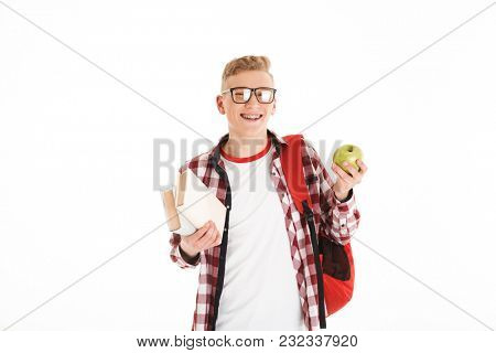 Portrait of a happy schoolboy in eyeglasses with backpack holding books and green apple isolated over white background