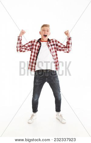 Full length image of shouting teen man wearing plaid shirt smiling and clenching fists on camera like winner or smart pupil isolated over white background