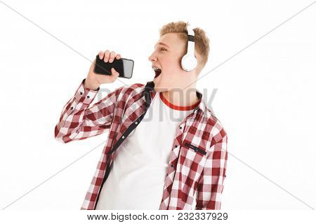 Joyous young man 17y in casual t-shirt listening to music via wireless earphones and singing using smartphone like microphone isolated over white background